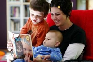 Mutte liest ihrem älteren Kind etwas vor, während Säugling auf ihrem Schoss sitzt.
